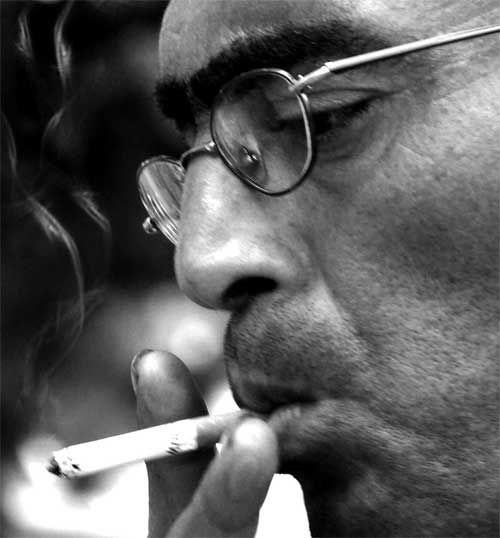 stressed man smoking a cigarette